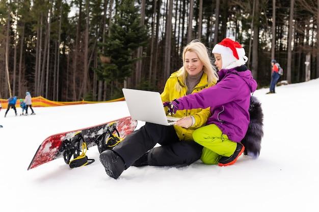 눈 덮인 산에서 노트북을 사용하여 스노보드를 들고 있는 엄마와 딸.