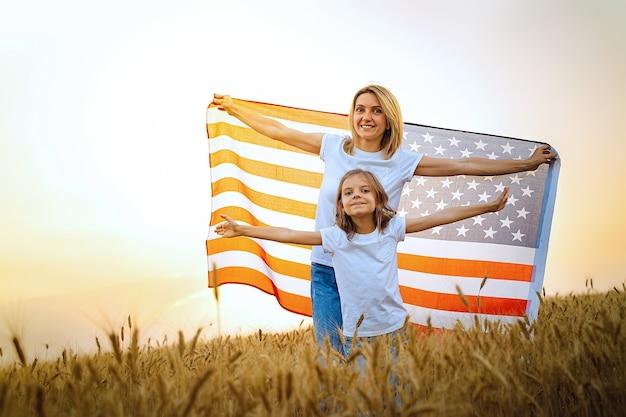Мать и дочь с американским флагом в красивом пшеничном поле