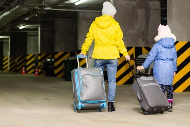 공공 지하 차고에서 가방과 어머니와 딸.