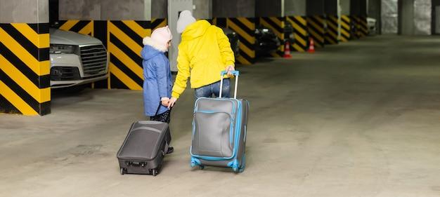 공공 지하 차고에 가방을 든 엄마와 딸.
