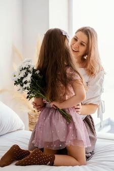 春の花の花束を持つ母と娘