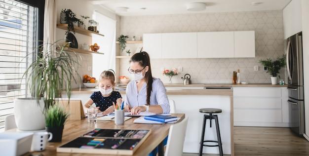 마스크를 쓴 엄마와 딸은 집에서 실내 학습, 코로나 바이러스, 검역 개념을 학습합니다.