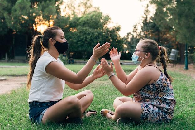 公園で遊んでいるフェイスマスクを持つ母と娘。