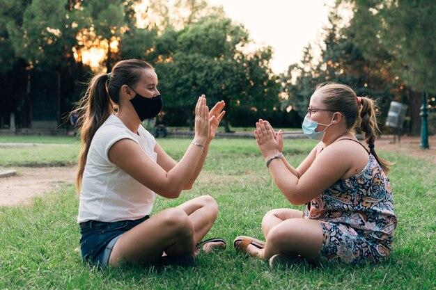 어머니와 딸이 공원에서 재생 얼굴 마스크.