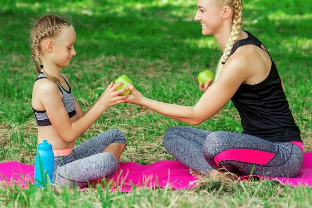 Мать и дочь с зелеными яблоками в парке.