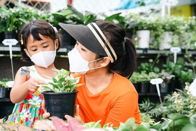 木の店で鉢植えを保持している健康なフェイスマスクを持つ母と娘