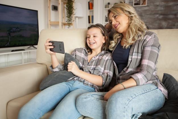 スマートフォンで面白いビデオを見ているソファに座って一致する服を着た母と娘。