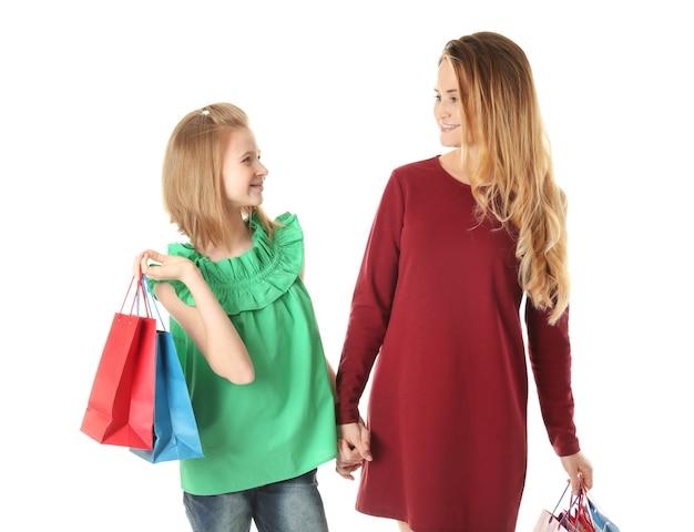 Мать и дочь с бумажными пакетами на белом