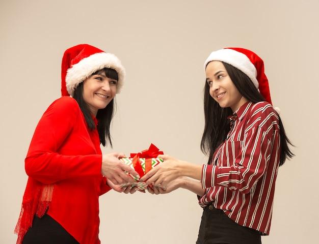 サンタの帽子とギフトボックスを持つ母と娘