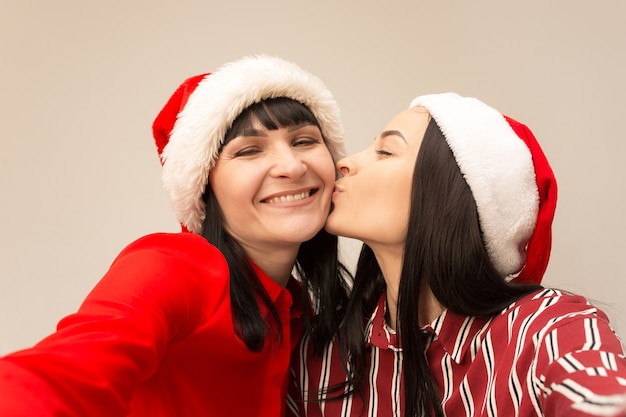 Мать и дочь с поцелуями шляпы санты.