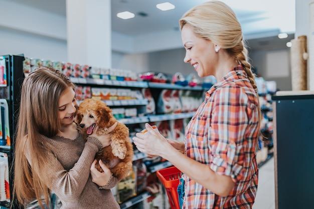 애완 동물 가게에서 푸들 강아지와 함께 엄마와 딸.