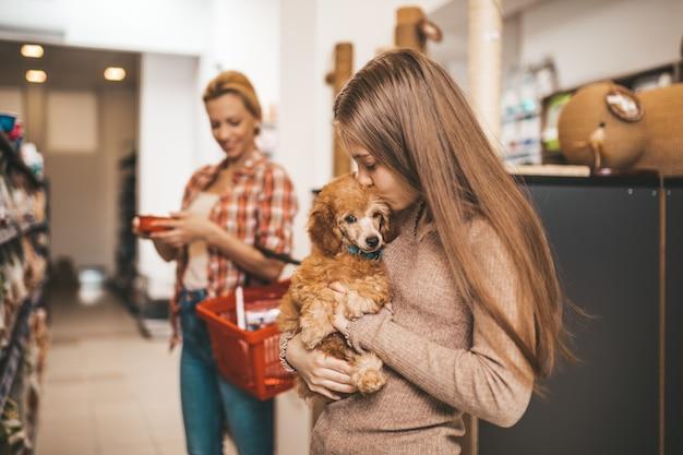 ペットショップでプードルの子犬と母と娘。