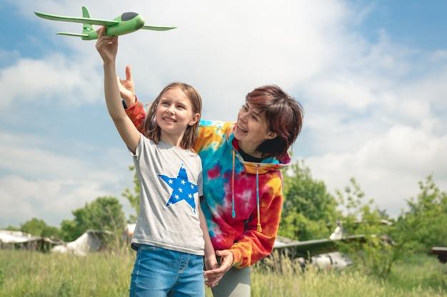 背景の女の子と女性の本物の飛行機とフィールドでおもちゃの飛行機を持つ母と娘