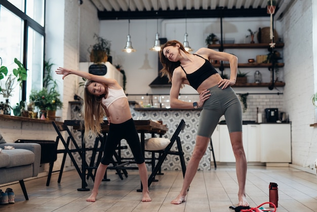 母と娘は家で運動し、横に立って曲がります。