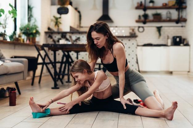 母と娘は家で一緒に運動します。