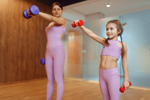 Мать и дочери делают упражнения с гантелями в тренажерном зале, фитнес-тренировки. мама и маленькая девочка в спортивной одежде, совместные тренировки в спортивном клубе