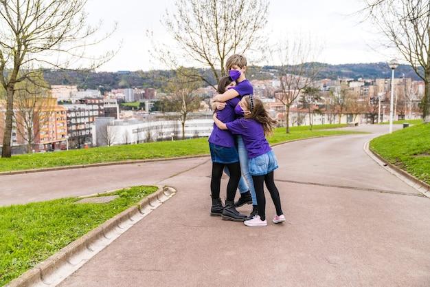 3月8日の国際女性デーに働く女性のシンボルが描かれた紫色のtシャツを着て、コロナウイルスのマスクを身に着けて、母と娘が通りで楽しく抱きしめました。