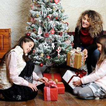 Мать и дочери открывают рождественские подарки