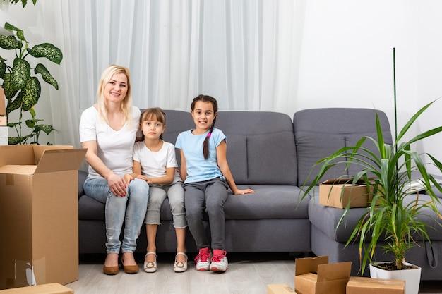 Мать и дочки упаковывают картонные коробки дома