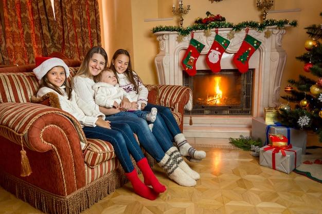 クリスマスのために飾られた家の燃える暖炉のそばのソファに座っている母と娘