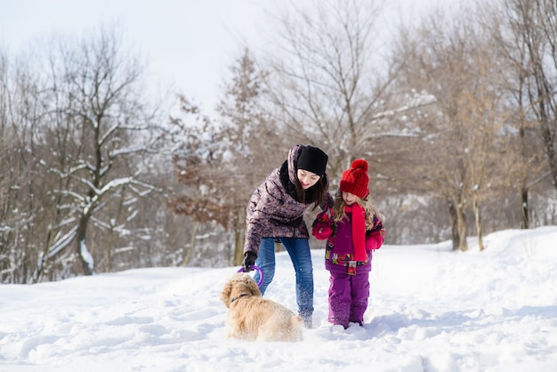 Мама и дочка играют с собакой в снежном лесу