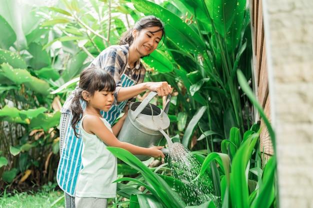 母と娘が一緒に庭に水をまく