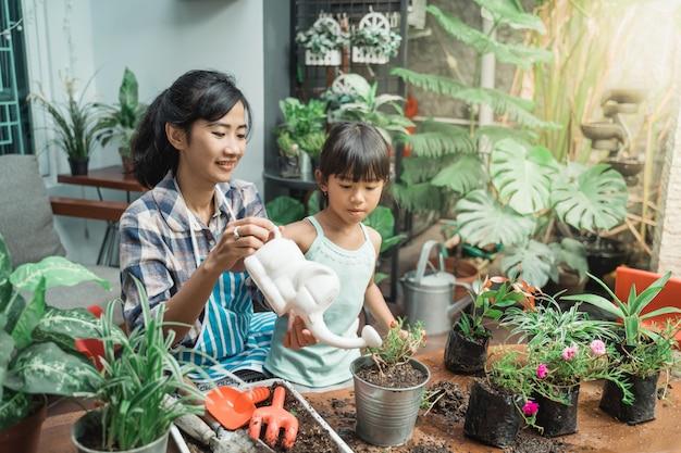 彼女の植物に水をまく母と娘