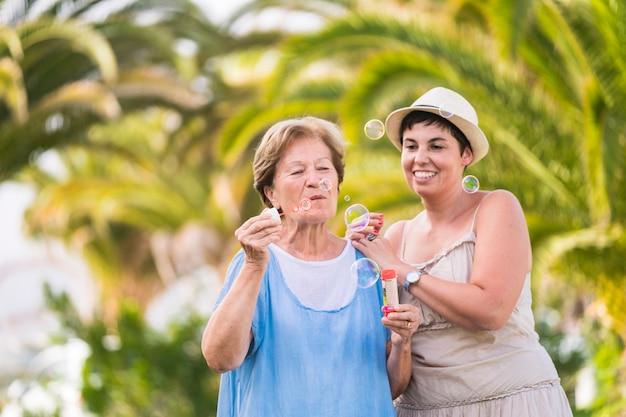 母と娘の白人カップルは、屋外のレジャー活動でシャボン玉を吹いて一緒に遊んでいます。焦点がぼけた自然の緑の背景。友情の中で一緒に幸せで遊び心のある人々の肖像画