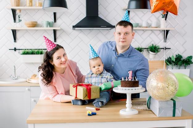 어머니와 아버지 집 부엌에서 아기의 첫 생일을 축하합니다. 케이크, 선물 상자, 파티 뿔 및 풍선으로 생일을 축하하는 행복한 가족