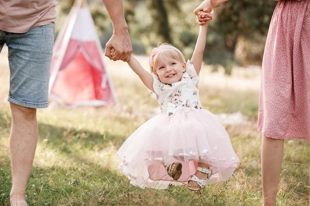 Мать и отец держатся за руки дочери, весело проводя время и гуляя в летнем парке