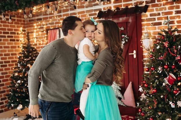 母と父は娘を手に持って彼女の頬にキスします