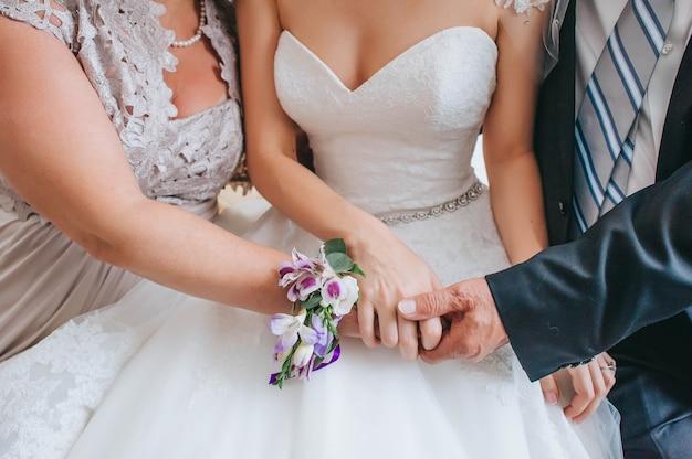 娘の手をつないでいる母と父-結婚式の日の若い花嫁。結婚式の家族。