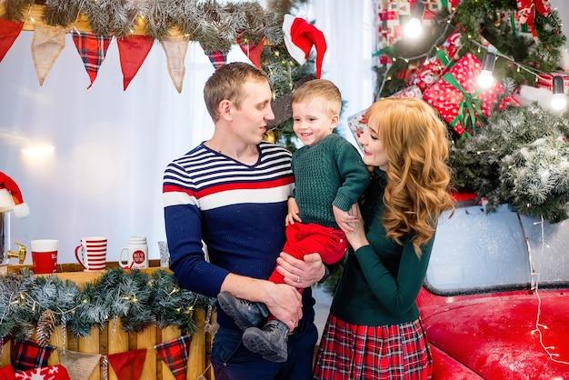 母と父は少年を抱きしめます。新年とクリスマス。幸せな家族は息子と楽しんでいます