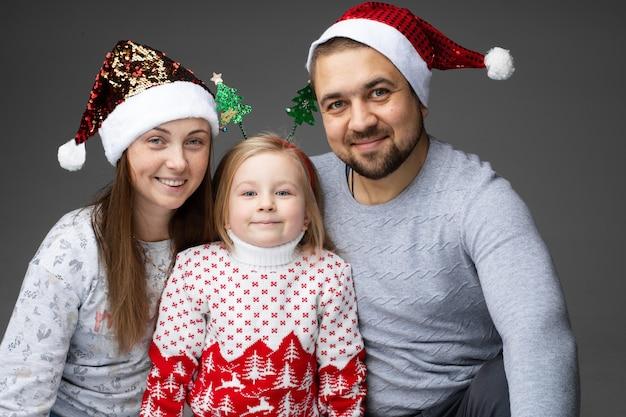 サンタの帽子をかぶった母と父、真ん中に娘が2本のクリスマスツリーのあるヘッドフープをかぶっています。