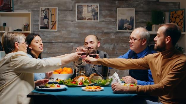 家族の夕食で子供たちと赤ワインのグラスをチリンと鳴らす60代の母と父。