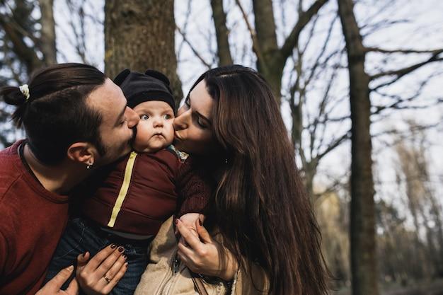 어머니와 아버지가 아기를 키스