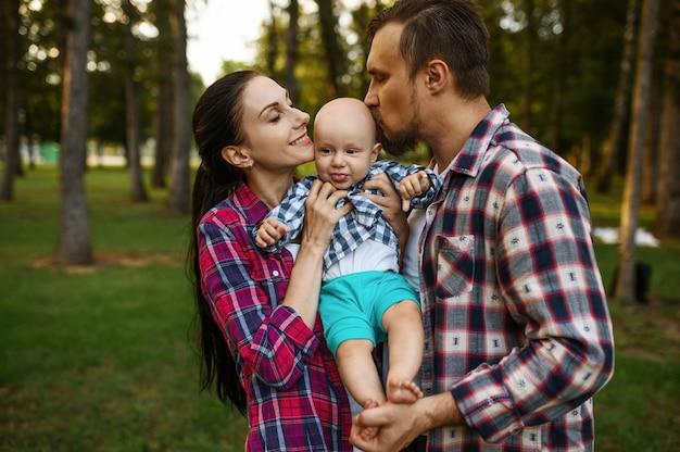 어머니와 아버지가 여름 공원에서 그들의 작은 아기를 키스