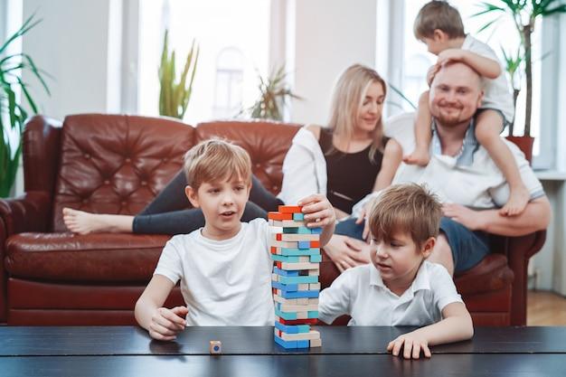 어머니와 아버지는 자녀와 함께 노는 동안 다른 두 아들은 테이블에 앉아 젠가 게임을 합니다.