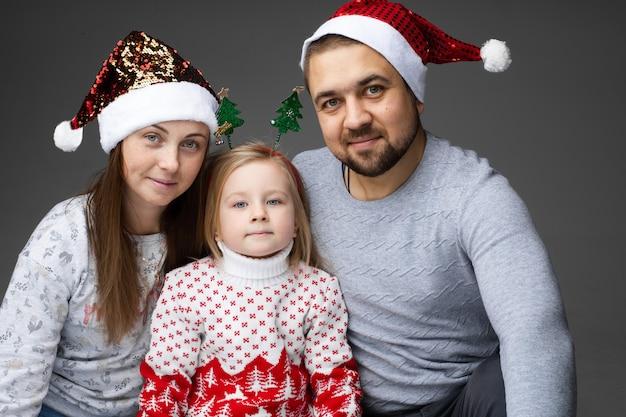 サンタの帽子をかぶった母と父、真ん中のかわいい娘がクリスマスツリーの頭のアクセサリーを身に着けています。
