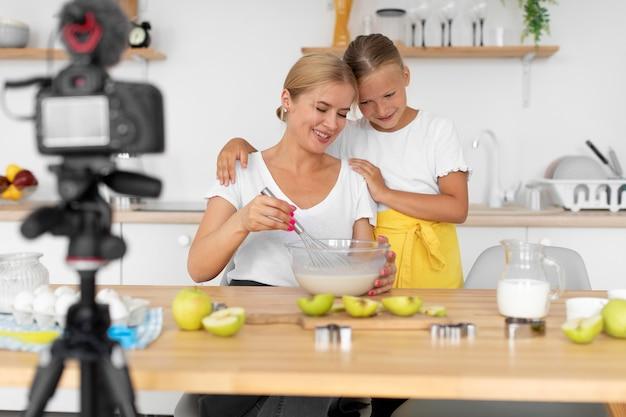 ミディアムショットを調理する母と女