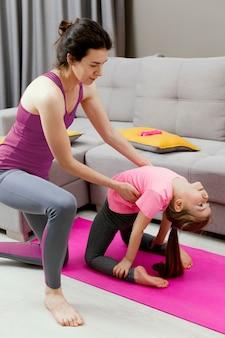 Мать и девочка занимаются спортом дома