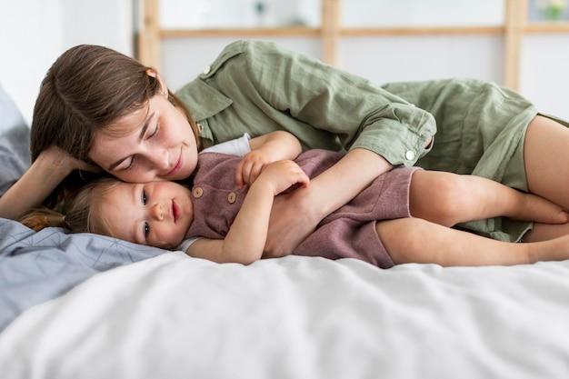 母と少女がベッドに敷設