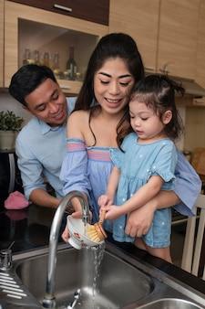 Мать и девочка моют посуду средний план