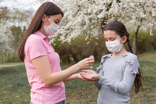 母と屋外のマスクを持つ少女