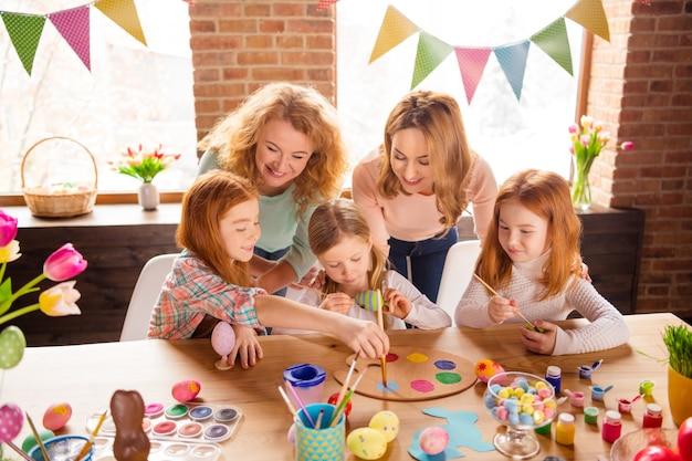 子供たちが絵を描くのを手伝う母と祖母