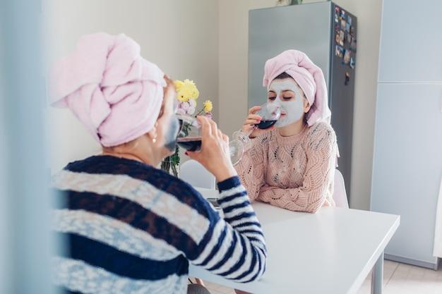 얼굴 마스크 적용 와인을 마시는 어머니와 그녀의 성인 딸. 식히고 부엌에 말하는 여자