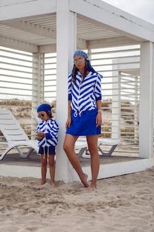 縞模様の青いジャケットを着た母と彼女の赤ん坊の息子は、木製の望楼の隣のビーチに沿って歩きます