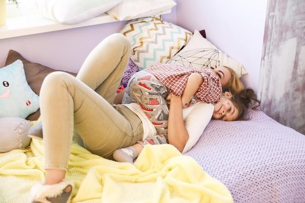 Мать и ее ребенок с удовольствием играют на диване, одетые в повседневную одежду