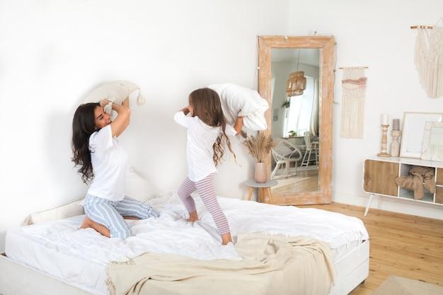 Мать и ее маленькая девочка борются с подушками