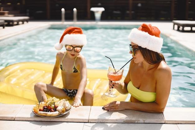 プールでクリスマスの帽子をかぶった母と彼女の子供。エキゾチックな国の休日。